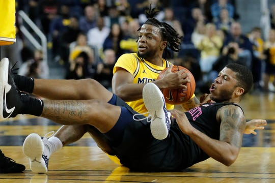 Michigan's Zavier Simpson and Penn State's Myles Dread tie up the ball in the first half at Crisler Center on Wednesday.