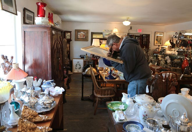 A shopper examines a framed item at Treasure Mart in Ann Arbor with three floors of fun. Dishes, furniture, and many other treasures can be found.Wednesday, May 18, 2016