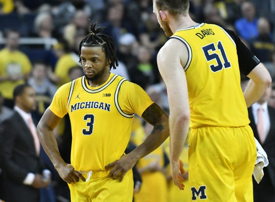 Michigan guard Zavier Simpson (3) heads to the bench for a timeout with Michigan forward Austin Davis (51) in the second half Wednesday night in Ann Arbor.