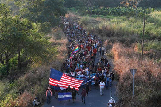 Central American migrants walk carrying a handmade U.S. flag and banners, after crossing the Suchiate River from Guatemala in Ciudad Hidalgo, Mexico, Thursday, Jan. 23, 2020.