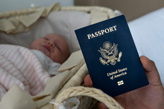 In this photo taken on Jan. 24, 2019, Denis Wolok, the father of 1-month-old Eva's father, shows the child's U.S. passport during an interview with The Associated Press in Hollywood, Fla.