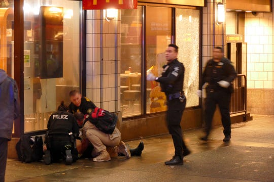Officers attend to one of several shooting victims, outside of McDonald's on Third Avenue, Wednesday, Jan. 22, 2020, in Seattle.
