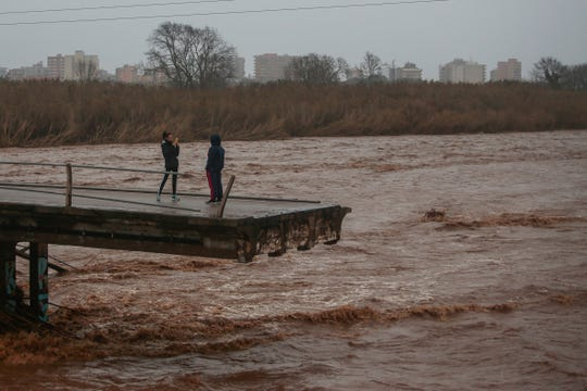 Two people take snapshots atop of a collapsed bridge in Malgrat, near Barcelona, Spain, Wednesday, Jan. 22, 2020.