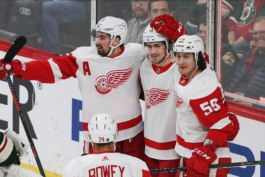 Red Wings forward Filip Zadina, center, is congratulated by Dylan Larkin, left, Tyler Bertuzzi and Madison Bowey on his first of Zadina's two goals against Wild goalie Devan Dubnyk in Wednesday's 4-2 loss in St. Paul, Minn.