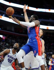 Pistons' Reggie Jackson scores over Kings' Bogdan Bogdanovic, right, and Harrison Barnes in the second quarter. Jackson had 22 points and four assists.