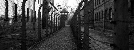 A pathway leading to an observation and security tower between what were electric barbed wire fences inside the former Nazi death camp of Auschwitz I in Oswiecim, Poland, Sunday, Dec. 8, 2019.