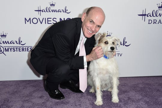 FILE - This July 26, 2018 file photo shows Bill Abbott, left, with a dog named Happy at Hallmark's Evening Gala during the TCA Summer Press Tour in Beverly Hills, Calif.