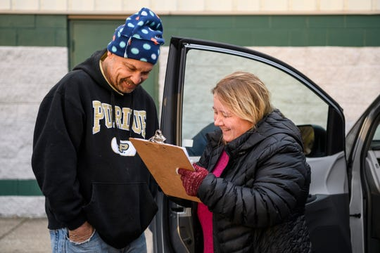 "David Bonham, left, answers questions from Carrie Burress, the Aurora outreach case manager, as she fills out a point-in-time survey outside of the Aurora Evansville office, Thursday morning, Jan. 23, 2020. ""I'm out here talking to everybody,"" Burress said. ""You have to connect with them, build a rapport with them. That's the only way they're going to trust us enough to let us help them."""