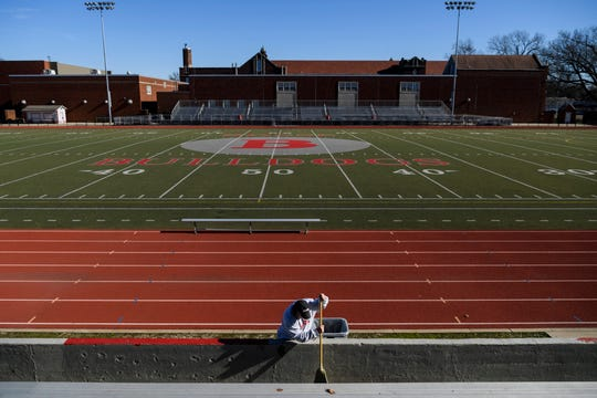 """Bosse's """"Yardman"""" Tommy Garrett sweeps leaves off of the bleachers at Enlow Field, Wednesday morning, Jan. 8, 2020. He is in charge of maintaining the old football stadium, which is used by Bosse and the neighboring catholic high school Memorial."""