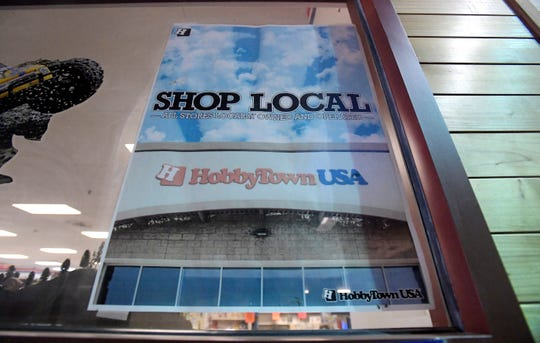 A sign hangs in the window at HobbyTown USA calling for people to shop locally in Fort Collins, Colo. on Wednesday, January 22, 2020. The store will be open though the end of January.