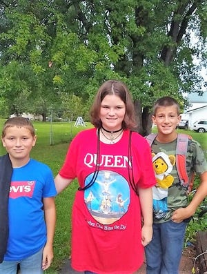Siblings Nic DeCoursin, Jeri Schroeder and Dalton Schroeder seen in the backyard of their home. They and their mother Katherine DeCoursin died Jan. 17 in a fire.