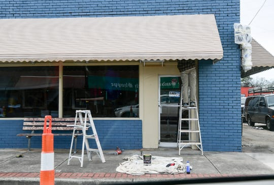 A painter works around an awning on the corner of Townville Street and West North First Street in downtown Seneca, where Mayberry's Restaurant is preparing to open in mid-March.