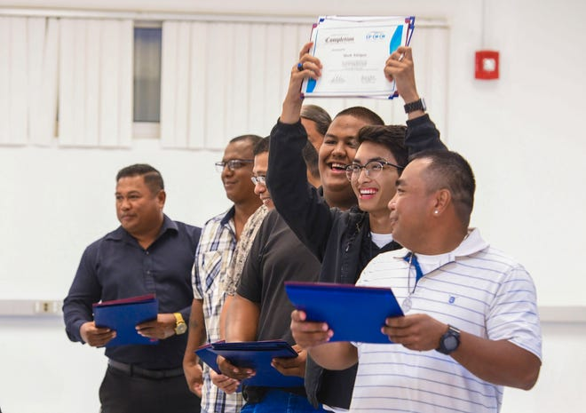 Mark Atoigue hoists his certificate of completion as he and six other Truck Driving Transportation Boot Camp participants are recognized for their completion of the 14-week course at the Guam Community College in this Jan. 23 file photo.