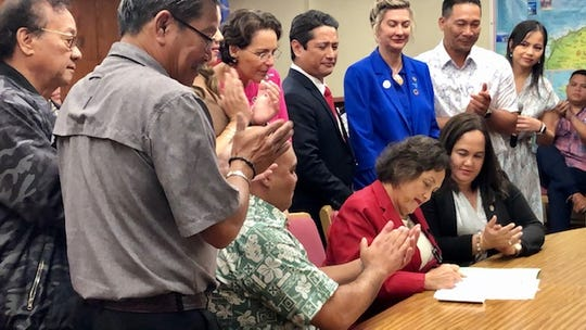 Gov. Lou Leon Guerrero signs a memorandum of agreement with the U.S. Treasury on Jan. 23, 2020, paving the way for GovGuam to start processing the payment of adjudicated war claims by still-living World War II survivors using nearly $14 million in local funds, while other officials applaud. Also in the photo are Lt. Gov. Josh Tenorio, senators led by Speaker Tina Muna Barnes, the governor's chief of staff Tony Babauta, and press secretary Krystal Paco-San Agustin.