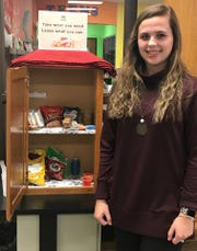 Hannah Grass poses next to The Little Food Pantry she spearheaded at the Henderson County Public Library (Jan. 23, 2020).