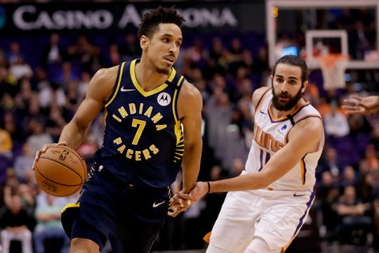 Indiana Pacers guard Malcolm Brogdon (7) drives past Phoenix Suns guard Ricky Rubio (11) during the first half of an NBA basketball game, Wednesday, Jan. 22, 2020, in Phoenix.