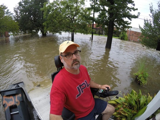 Scott Crawford, a Jackson resident and advocate for those with disabilities, takes a picture from his motorized wheelchair of flooding in front of his home on Choctaw Drive in Jackson. Crawford lives next to Eubanks Creek which often overflows onto his property.