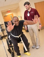 "Ed Thigpen adds a few squats at the end of his therapy session with Methodist Rehabilitation Center physical therapist Kollin Cannon. ""His approach was to come in with an athlete's work ethic,"" Cannon said of the former Ole Miss player. Thigpen went from barely able to stand  to walking out of the facility on Jan. 22, 2020."
