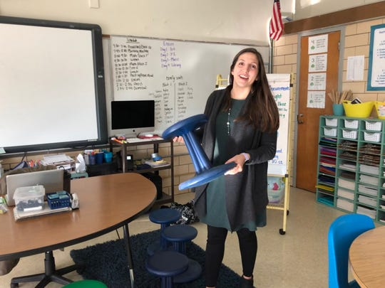 "Belle Morris' Teacher of the Year Caitlin Hatfield laughs as she shows off a ""wobble stool,"" part of the flexible seating in her open classroom. She says the stool allows the students to burn off energy while they're doing their work. ""It's not distracting,"" she says – actually quite the opposite. January 22, 2020."
