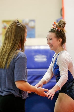 Harrison's Haiven Gipson reacts with coach Haley Sanders after competing on the floor exercise during a meet earlier this season.