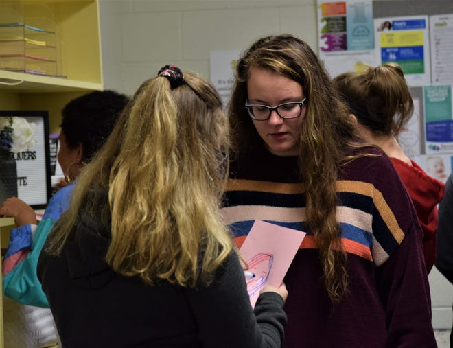Ella Clum, right, watches as a classmate draws her during an activity during the ROX meeting Jan. 15 at Lancaster High School. ROX is a non-profit organization designed to help girls learn how to be confident in themselves and learn how to express themselves.