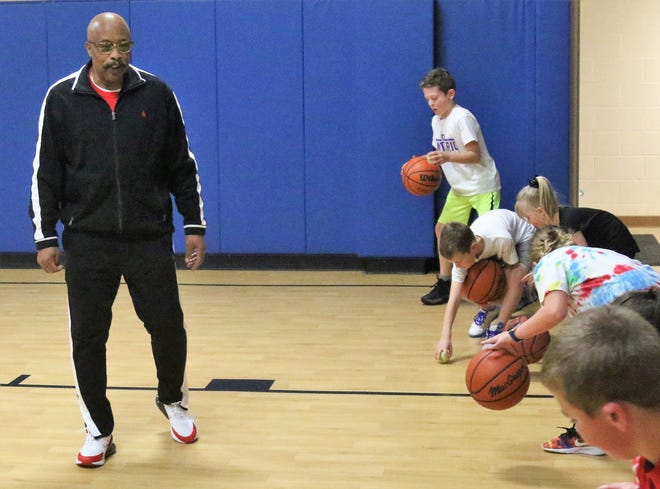 Erskine Braggs instructs and encourages during a dribbling drill at his skills clinic on Wednesday at the Mansfield Community Outreach Center.