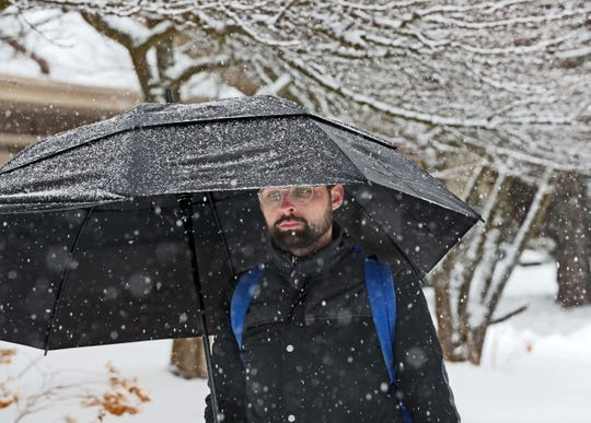 Grant Gill of Milwaukee, protects himself from the wet falling snow with an umbrella as he walked along Milwaukee's lakefront near Lake Park.