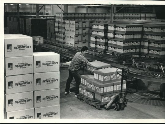 A temporary employee moves cases of chips at Geiser's Potato Chip Co., in 1986.