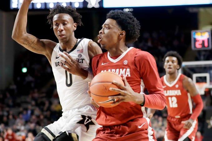 Alabama forward Herbert Jones, center, drives against Vanderbilt guard Saben Lee (0) in the first half of an NCAA college basketball game Wednesday, Jan. 22, 2020, in Nashville, Tenn. (AP Photo/Mark Humphrey)