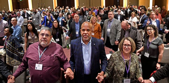 Delegates to the pre-General Conference of The United Methodist Church hold hands as they sing during worship in Nashville, Tenn. Thursday, Jan. 23, 2020.