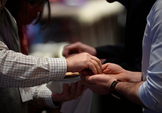 Delegates receive Communion during morning worship at the pre-General Conference of the United Methodist Church in Nashville on Jan. 23, 2020.