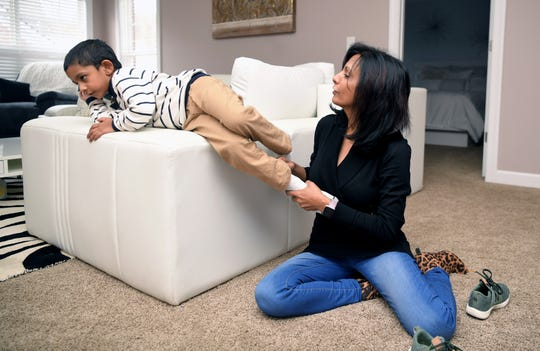 Dr. Sowmini Oomman struggles to put socks and shoes on her squirming 5-year-old son, Dante, at their Franklin home Wednesday, Jan. 22, 2020. Dante has autism, and Oomman and her husband, Dr. Sujay Kumar, want to build car washes to give jobs to adults with autism.