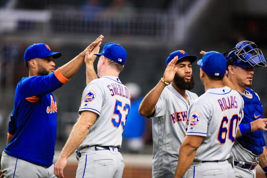 Mets coaches Glenn Sherlock (53) and Luis Rojas (60) congratulate players Robinson Cano, Amed Rosario and catcher Wilson Ramos following their 10-8 win over the Atlanta Braves at SunTrust Park on August 15, 2019 in Atlanta, Georgia.