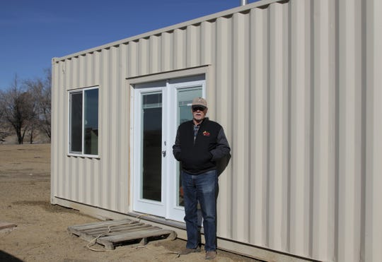 Larry Waldroup stands outside a shipping container house, Thursday, Jan. 23, 2020, in Kirtland.