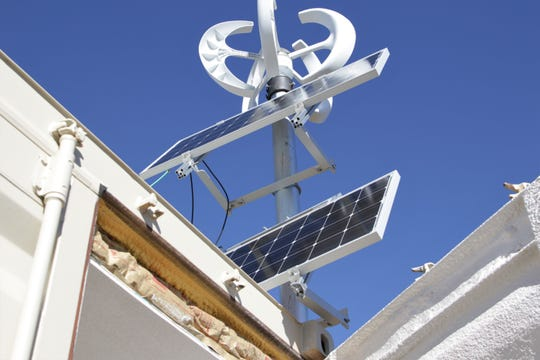 Solar panels and a small wind turbine are located on a shipping container home in Kirtland.