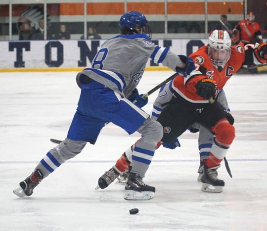 Brother Rice captain DJ Dixon tries to fight through the defense of Shamrock Kaden Hemme to get to a loose puck.