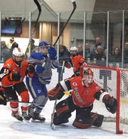 Brother Rice goalie Cooper Duncan keeps an eye on the puck as a bunch of players whip by his net.