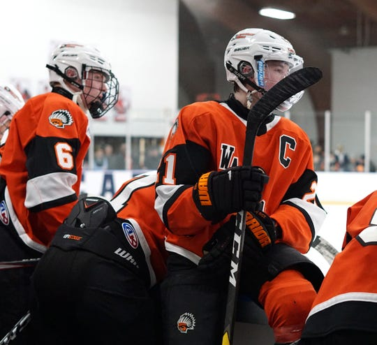 Brother Rice hockey players watch their teammates on the ice from the bench.