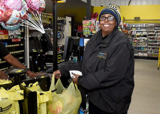 Dollar General customer Brenda Sonnier of Port Barre leaves the newly-relocated Dollar General store with a basket of household items purchased Thursday morning.