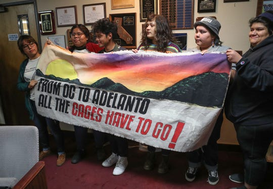 Opponents against turning the Desert View Correctional Facility into an Immigration and Customs Enforcement detention facility hold a sign during an Adelanto Planning Commission meeting, January 22, 2020.