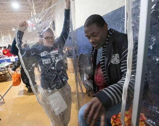 Hayley Brown helps Carlos Pariss as he climbs out of a hurricane wind simulator Thursday at the U-Count Homeless Resource Day at the Salvation Army.