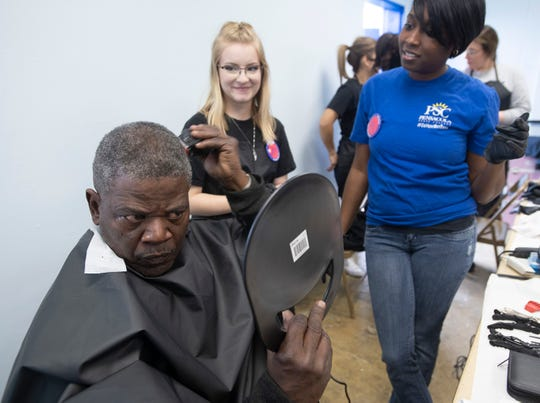 Samuel Robinson adds a few finishing touches to his haircut as Pensacola State College student Willow Kapke and instructor Minisha Carter look on during the U-Count Homeless Resource Day on Thursday at the Salvation Army in Pensacola.