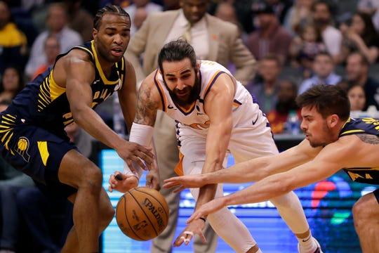 Phoenix Suns guard Ricky Rubio, center, loses the ball as Indiana Pacers forward T.J. Warren, left, and Indiana Pacers guard T.J. McConnell defend during the second half of an NBA basketball game, Wednesday, Jan. 22, 2020, in Phoenix. (AP Photo/Matt York)