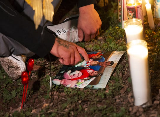 Pedro Rios, the father of three young children who police say were killed by their mother, touches a photo at a makeshift memorial outside his house in Phoenix on Jan. 22, 2020. Phoenix police say Rachel Henry admitted she killed her children.