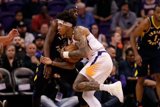 Phoenix Suns forward Kelly Oubre Jr., right, fouls Indiana Pacers guard Aaron Holiday as he drives to the basket during the first half of an NBA basketball game, Wednesday, Jan. 22, 2020, in Phoenix. (AP Photo/Matt York)