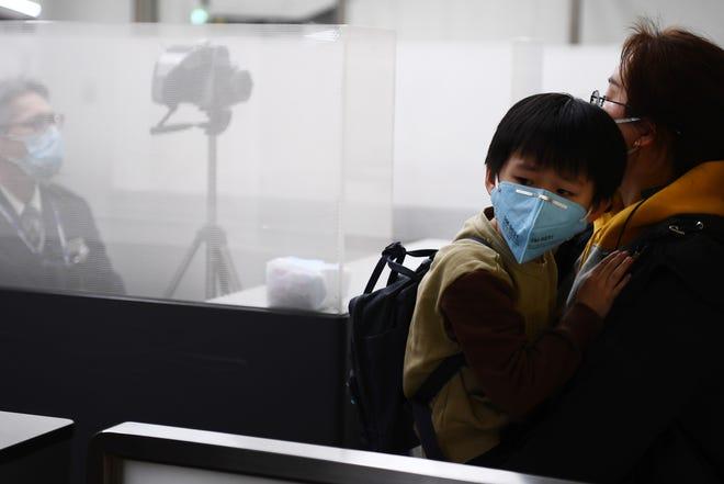 Una mujer y su hijo pasan por un punto de inspección en el aeropuerto.