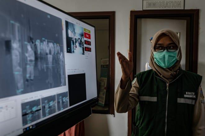 Una mujer monitorea los chequeos en una cámara, en el aeropuerto de Indonesia.