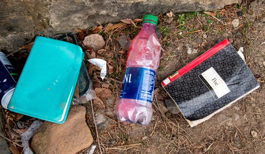 The Bible and a poetry book are among the many personal items discovered by the creek as evidence that someone may be living there.
