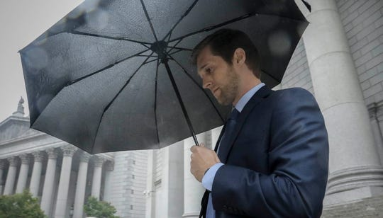 Cameron Collins, son of former U.S. Rep. Chris Collins, covers with an umbrella as he leaves court Oct. 3, 2019. He was sentenced to five years of probation on Thursday for his role in the insider trading scheme that brought down his father.