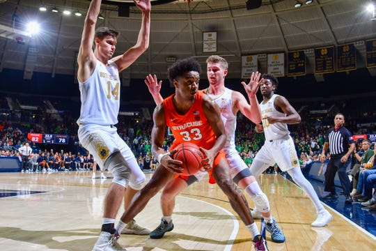 Syracuse Orange forward Elijah Hughes (33) dribbles as Notre Dame Fighting Irish forward Nate Laszewski (14) and guard Rex Pflueger (0) defend in the second half at the Purcell Pavilion. Hughes scored 26 points in Syracuse's 84-82 victory.